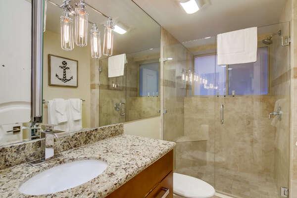 Guest Bathroom with walk in shower, vanity sink, and toilet.
