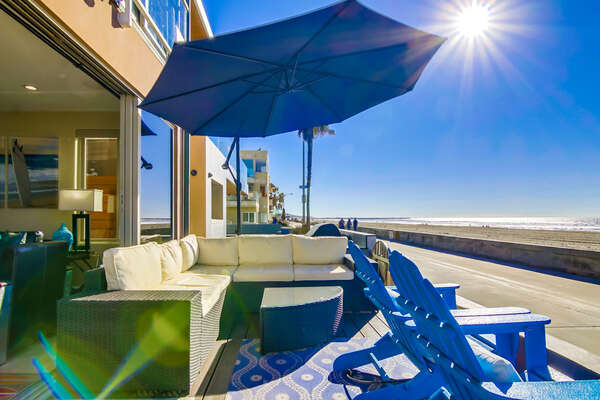 Oceanfront Patio with large umbrella covering a sectional outdoor couch.
