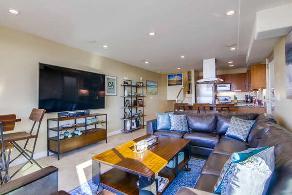 Living Room on the Ground Floor with large TV, couches, and coffee table.