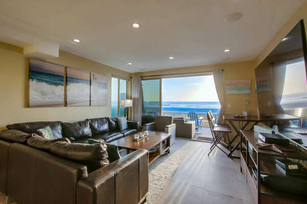 Living area with leather couches, and a large sliding glass door opening to the patio.