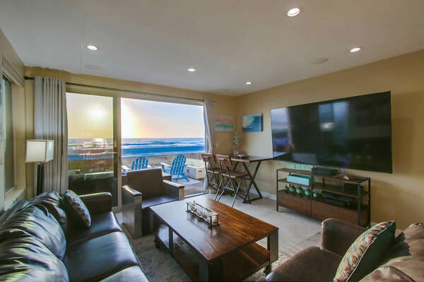 Picture of the living area, highlighting its large wall mounted TV and ample seating.