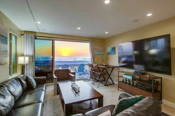 Living area of this San Diego vacation home rental, with two couches and a massive wall-mounted TV.