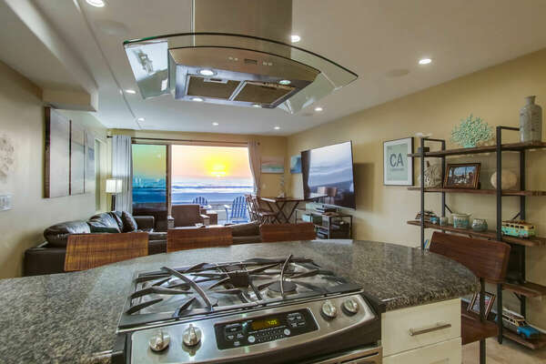 Picture taken from inside the kitchen, displaying its island range and ocean views.