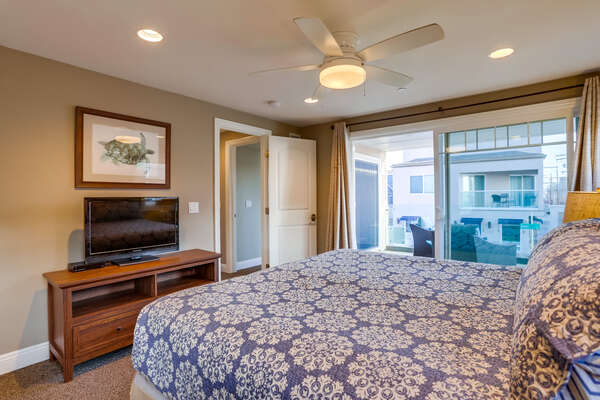 Bedroom with Large Bed, TV, TV Stand, Ceiling Fan, and Sliding Doors.
