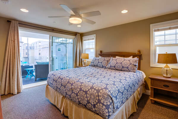 Bedroom with Balcony, Large Bed, Nightstands, Ceiling Fan, and Lamps.