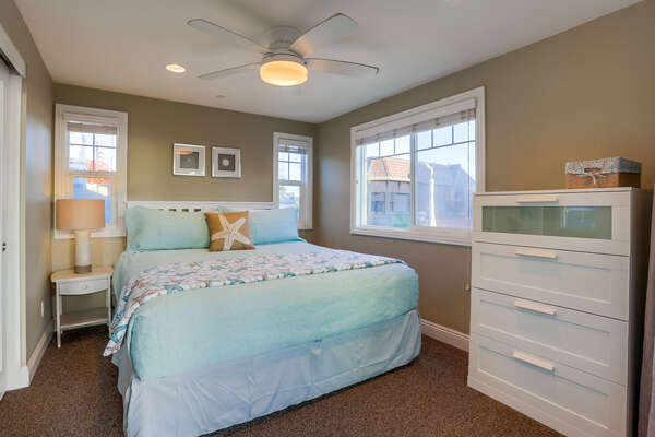 Bedroom with Large Bed, Dresser, Ceiling Fan, and Nightstand.