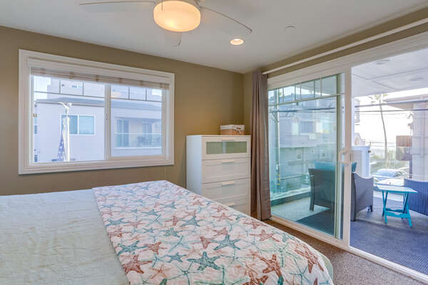 Large Bed, Dresser, Ceiling Fan, and Sliding Doors to the Balcony.