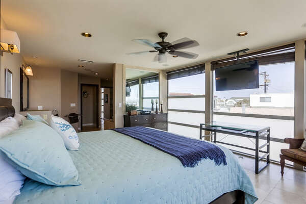 Third Floor Master Bedroom with large windows and an equally large bed across from a wall mounted TV.