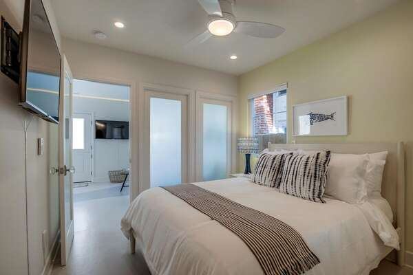Bedroom Includes Spacious Bed and TV on Wall.
