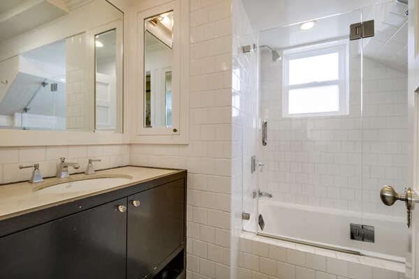 Bathroom with hallway access, shower/tub combo.