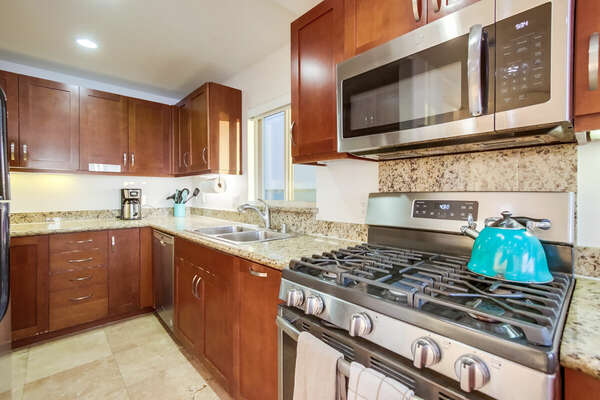 Fully stocked kitchen with gas stove and microwave