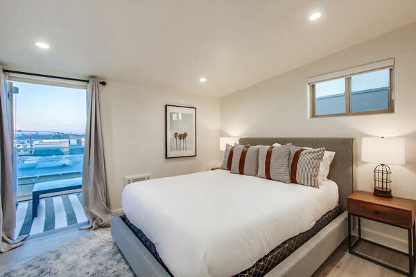 Guest bedroom with queen bed and balcony access - Upper level