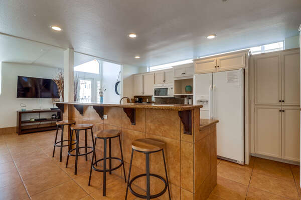 Breakfast Bar, Refrigerator, Pantry Doors, and TV.