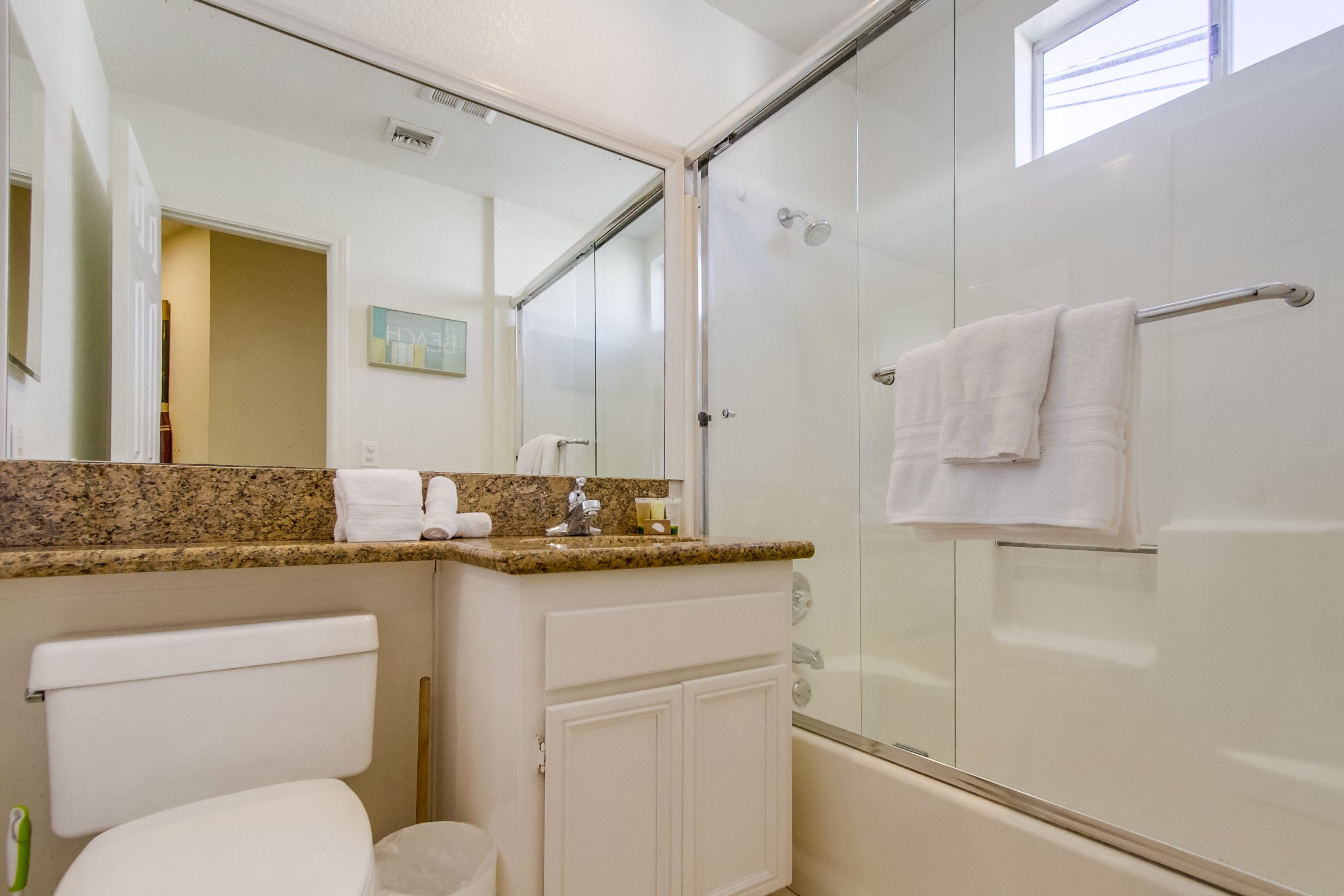 Bathroom with Shower-Tub Combo, Toilet, and Single Sink Vanity.