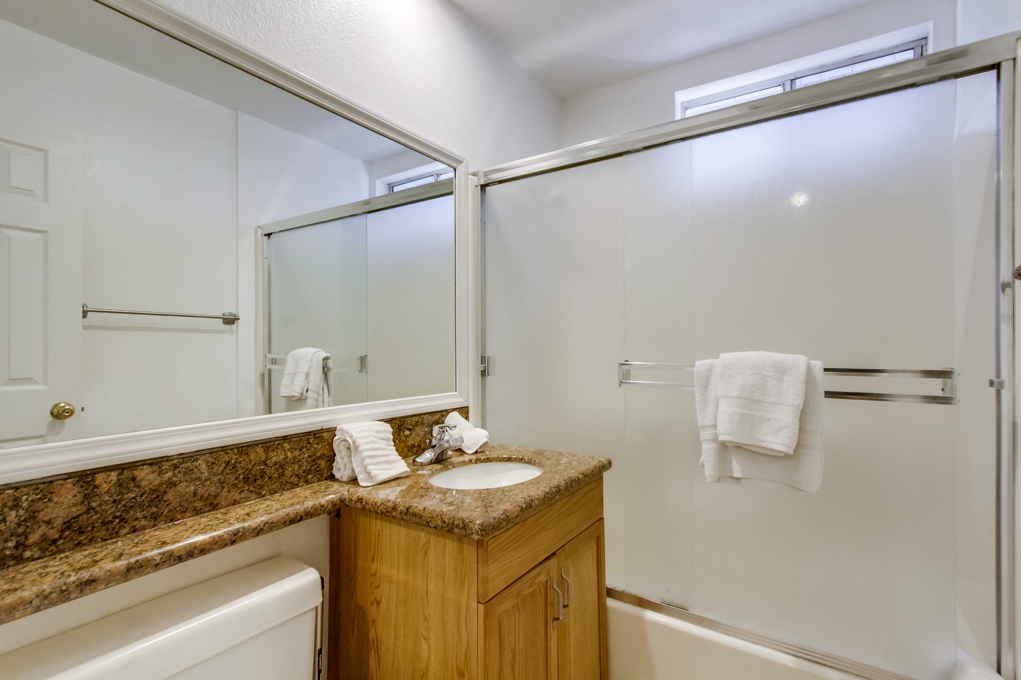 Single Sink Vanity, Mirror, and Shower-Tub Combo.
