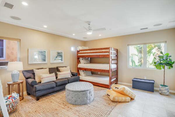 Spacious Common Area w/ Triple Bunk Beds, Plush Sofa, & Modern Finishings