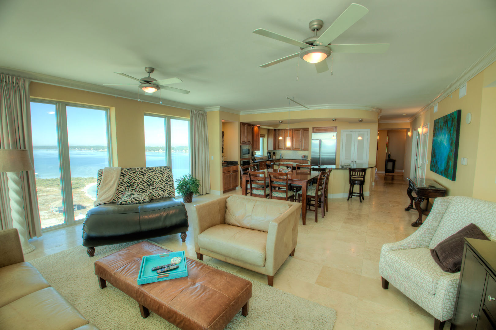 Sofa, Arm Chairs, Ceiling Fan, Windows, Dining Set, and the Kitchen.