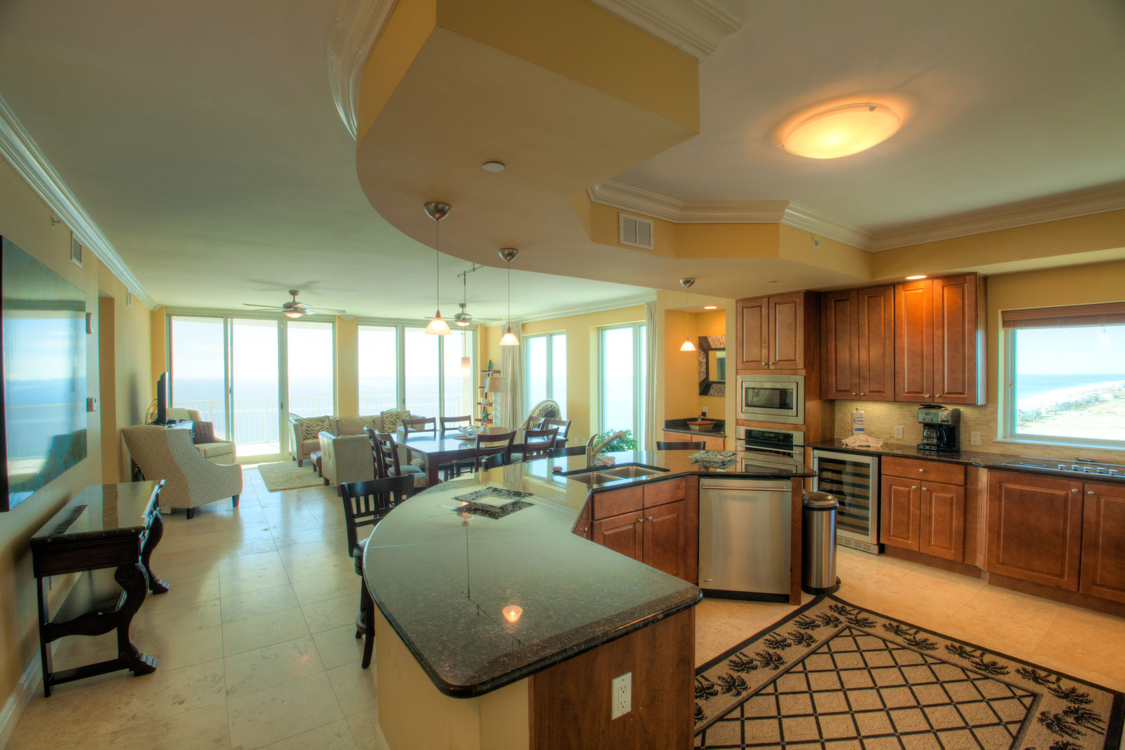 Kitchen with Island, Stools, Dishwasher, Wine Cooler, and Dining Set.