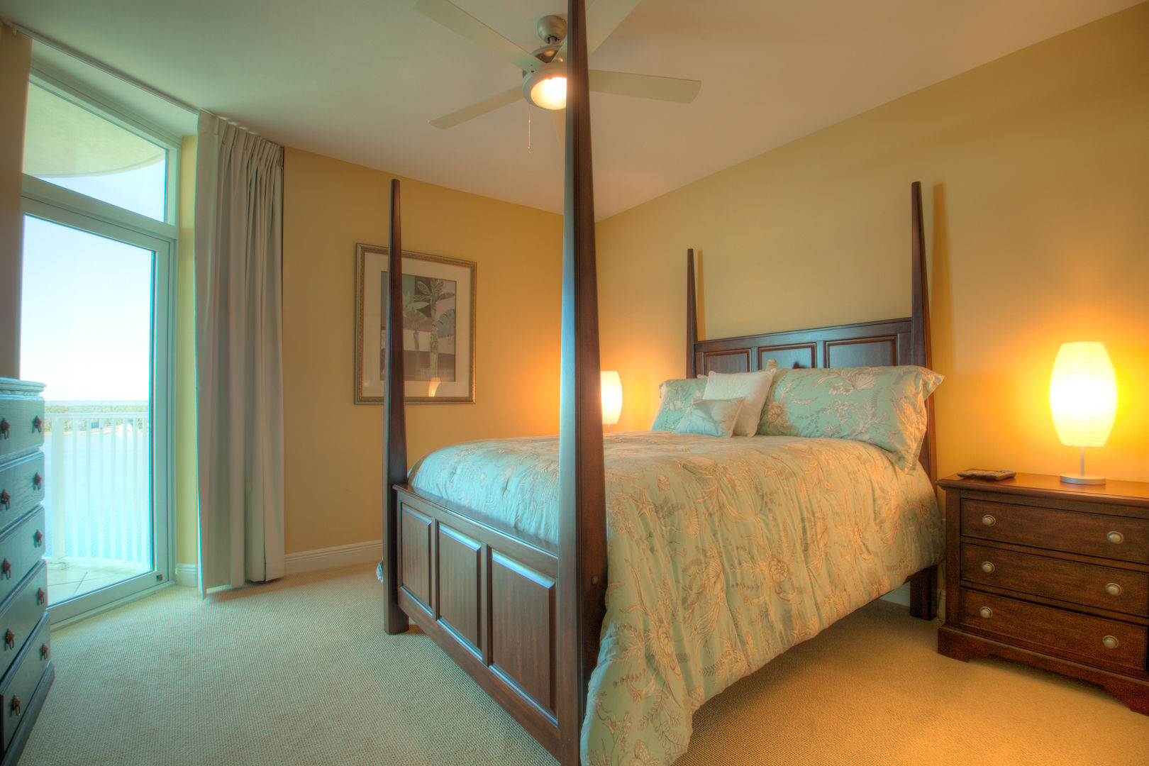 Large Bed, Ceiling Fan, Nightstand, Dresser, and Glass Door to the Balcony.