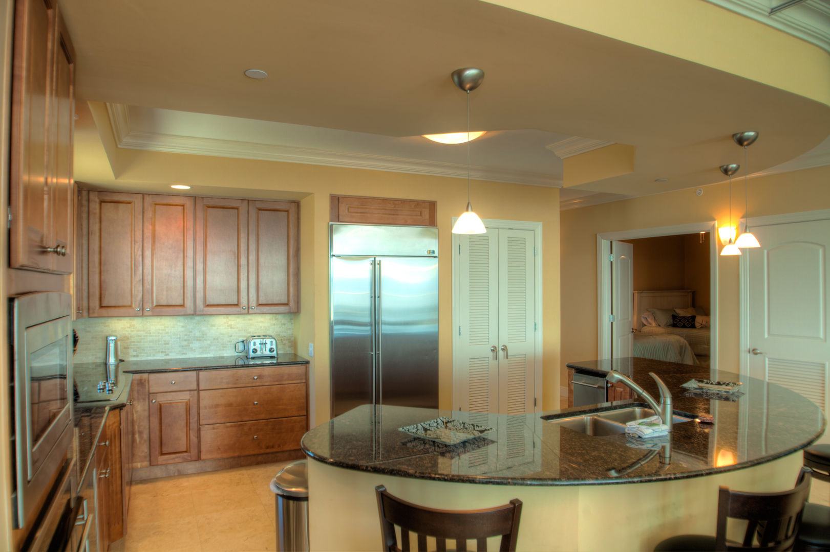 Kitchen with Island, Refrigerator, Microwave, and Pantry Doors.