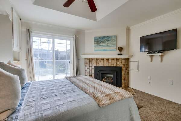 Second Floor-Suite with fireplace, wall mounted TV, and large bed.