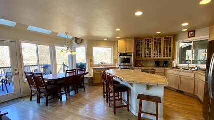 Spacious Kitchen with Tile Countertops, Stainless Appliances, Bar, and Dining Area