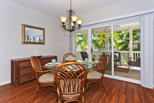 Dining Area with chairs, glass dining table, and dresser to the left, all in front of the sliding glass doors.
