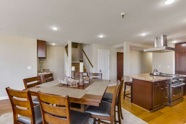 Dining Table, Chairs, Kitchen Countertop Bar, Stools, and Stove.