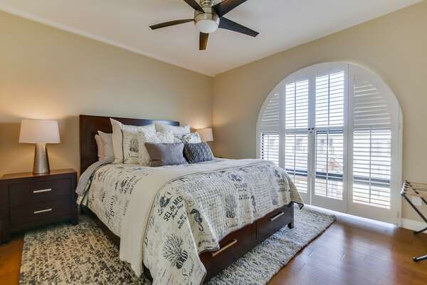 Bedroom with Large Bed, Ceiling Fan, Nightstands, Lamps, and Window.