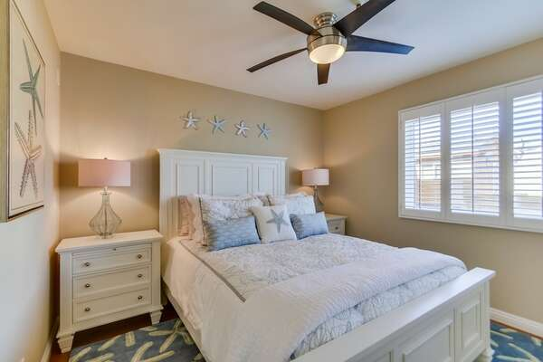 Bedroom with Large Bed, Nightstands, Table Lamps, and Ceiling Fan.