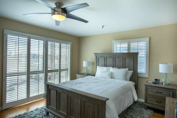 Bedroom with Large Bed, Nightstands, Lamps, Ceiling Fan, and Windows.