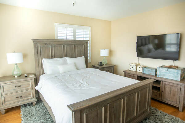 Large Bed, Nightstands, Lamps, TV, and Buffet Table.