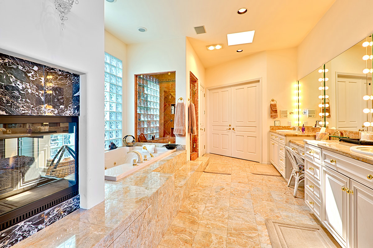 Master bathroom en suite with his and hers vanities, vanity chair, custom designed shower, separate tub, large walk-in-closet