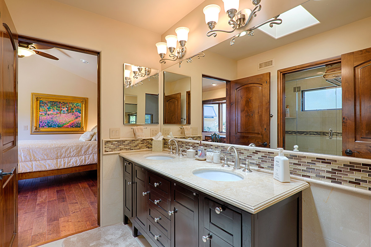 Guest bathroom shared between guest rooms with double sinks, private shower and toilet area