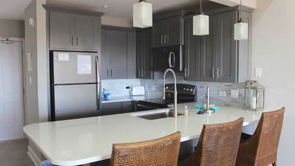 The upscale kitchen features seating at the granite counter.