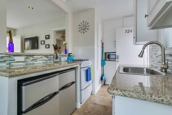 Cozy Kitchen with back door. 2 small (college sized) fridge/freezers, gas stovetop/oven/ microwave, and view of the flat screen tv in the living room