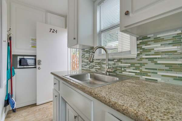 Kitchen with view to back screen door, lots of cabinets and microwave oven