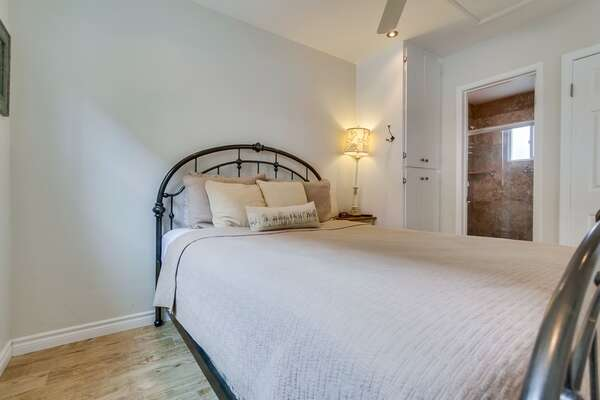 Queen sized bed with view into bathroom, ceiling fan,