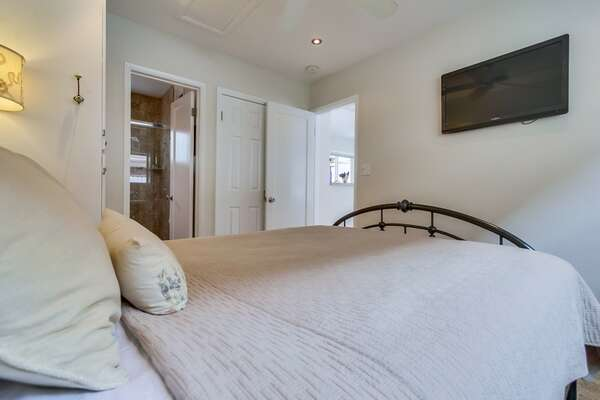 Queen sized bed with view into bathroom and living room, flat screen tv and closet