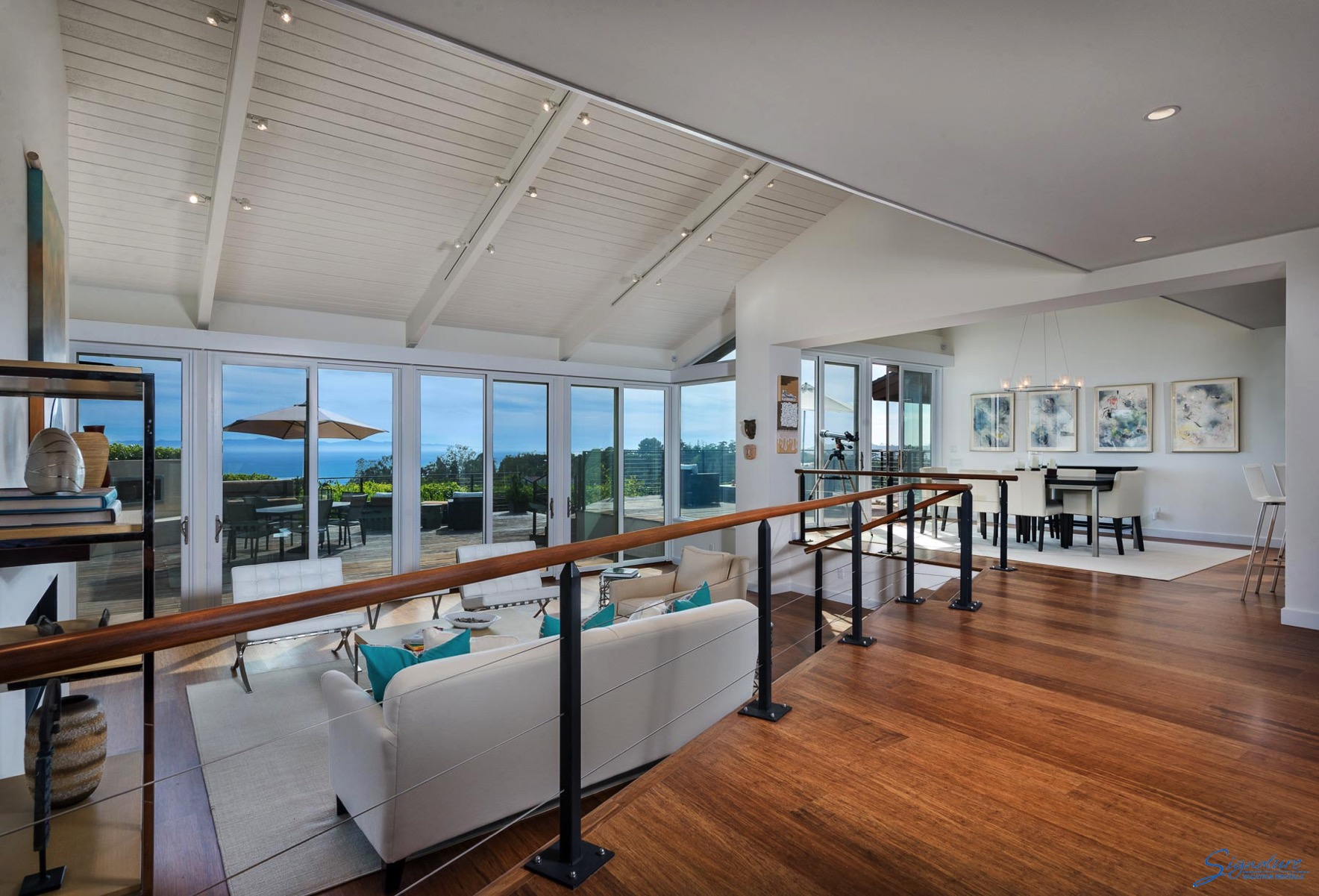The living room is light and bright with large plate glass windows framing the ocean views.
