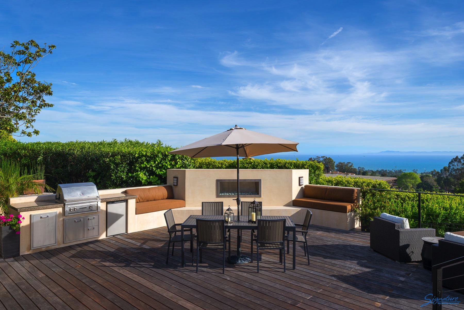 Large south facing deck with views of the ocean and the islands, gas fireplace and gas grill