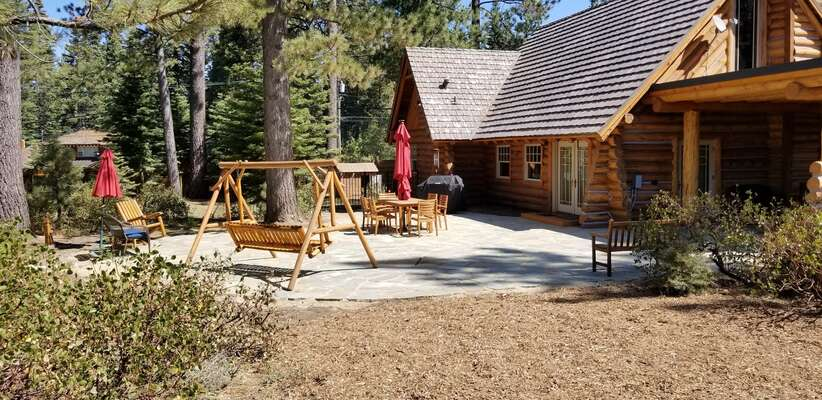 Rear stone patio surrounded by meadow and forest