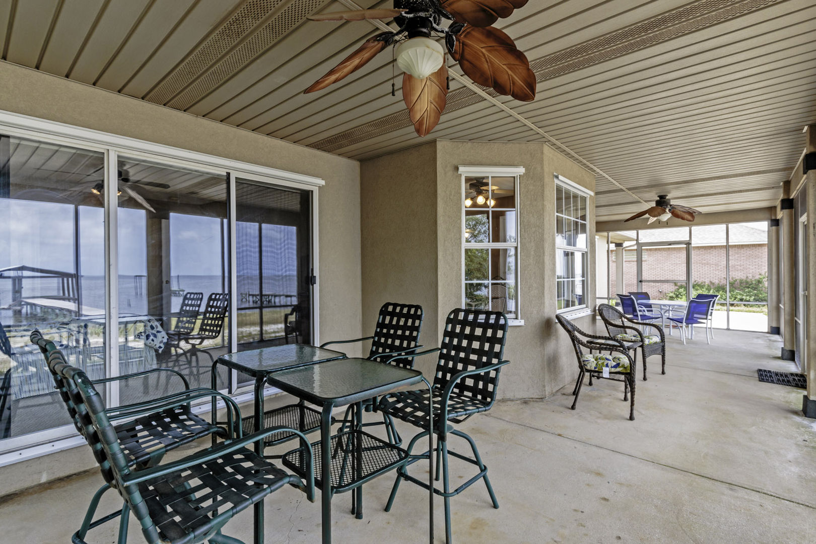 Another view of the spacious screened in porch and its seating.