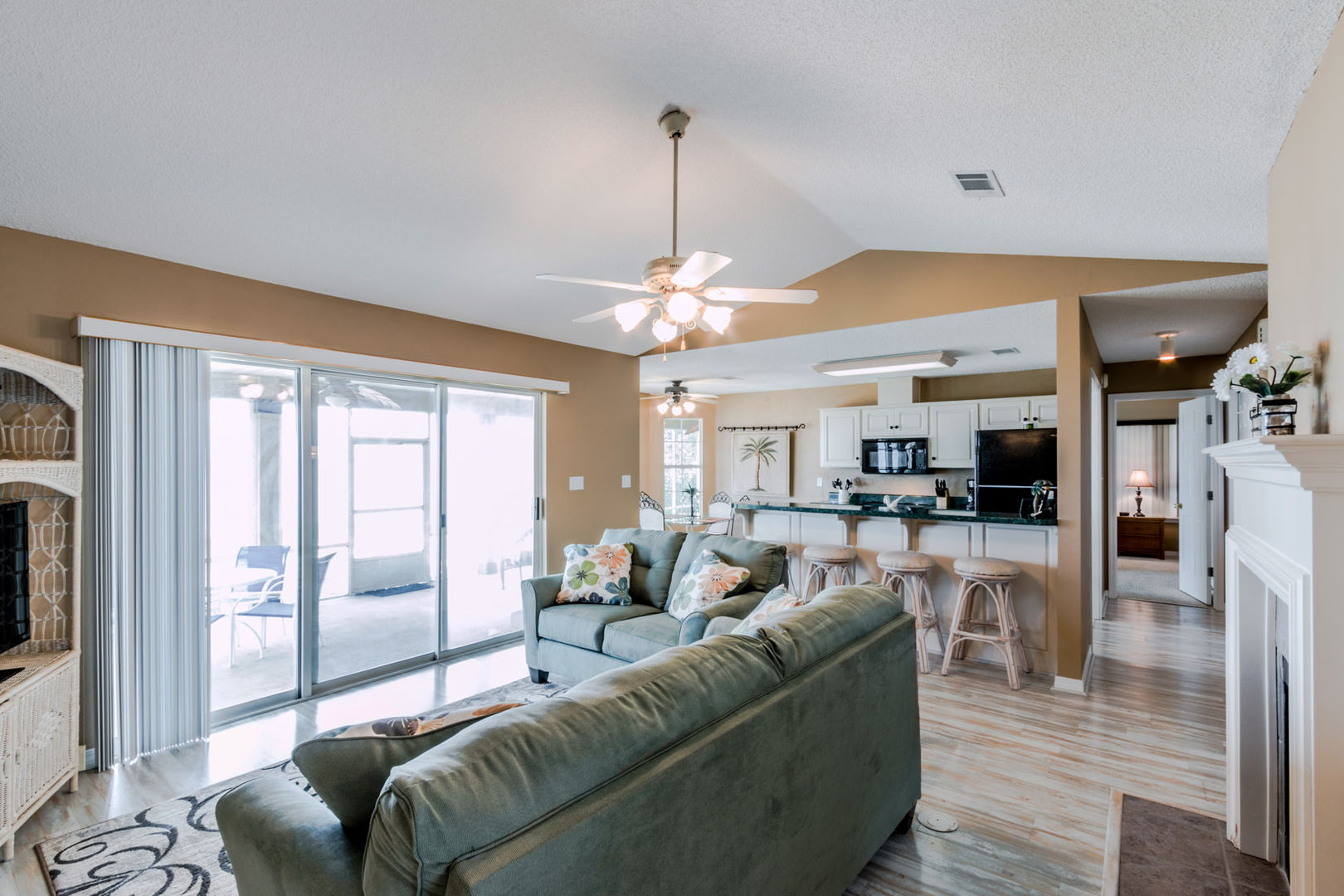 Spacious Living Area Overlooking The Bay, with couches and view of kitchen.