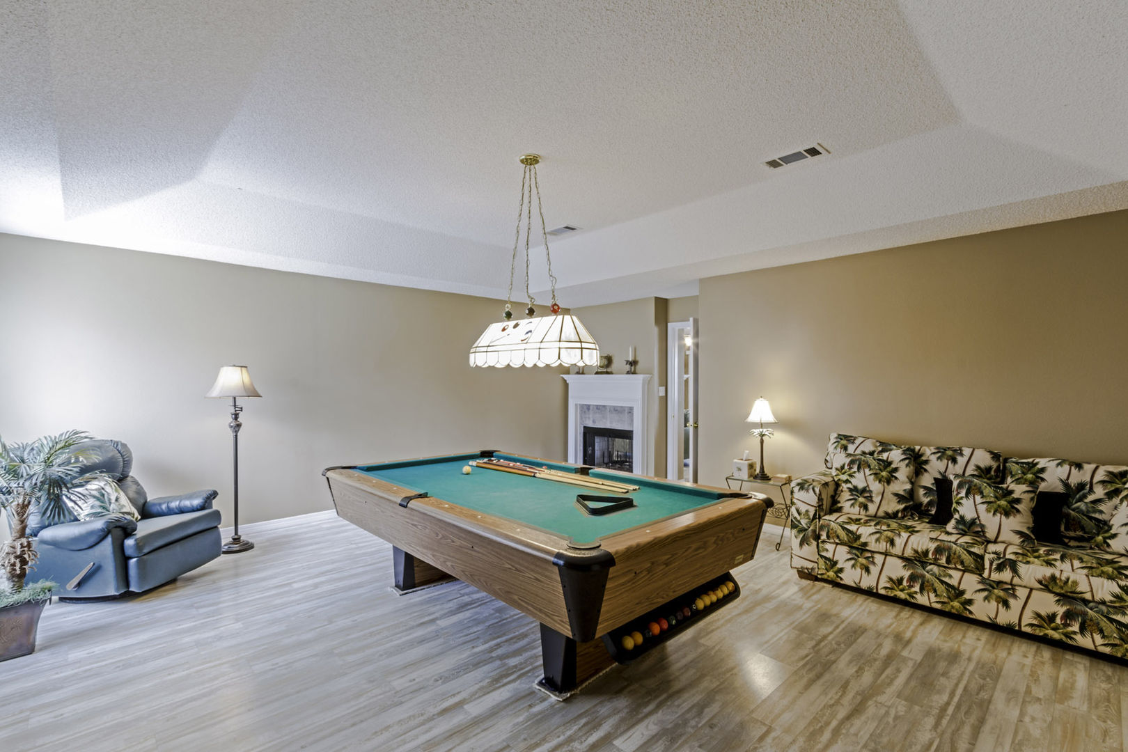 Gameroom with pool table and seating.