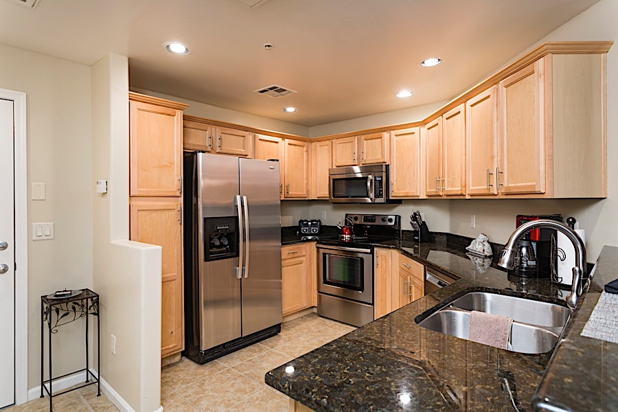 Kitchen w/ grainte counter tops, tile floor and stainless steel appliances.