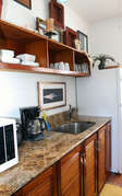 full kitchen with natural marble countertops and teak cabinets