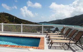 Lounge in sun with views of Coral Bay and a refreshing dip in the pool