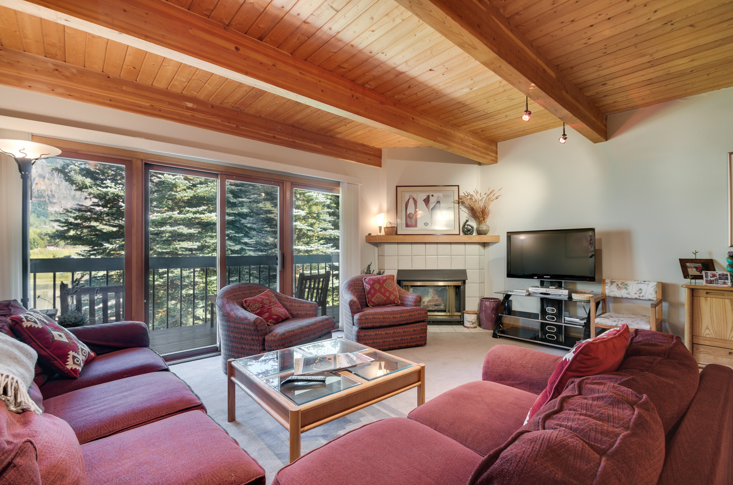 Living area to fireplace with comfortable sofa and chairs
