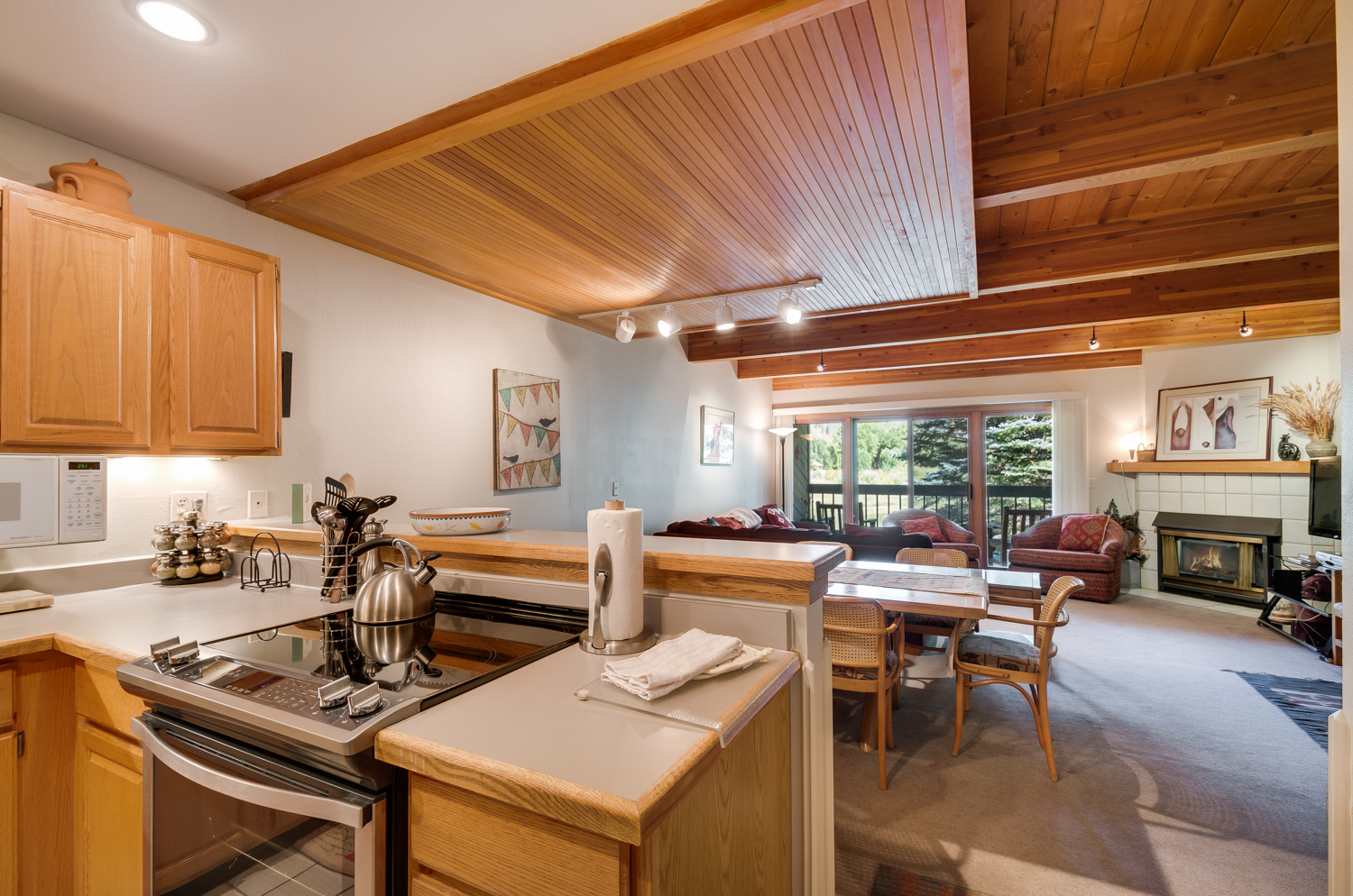 Kitchen to living area view with wood paneling and ceiling